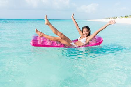 Plage fille fun ludique sur matelas piscine flottante rose flottant sur les vacances d'eau de l'océan escapade. femme Party applaudir jambes et les bras sur gonflable piscine de lit de jouet dans la mer turquoise.