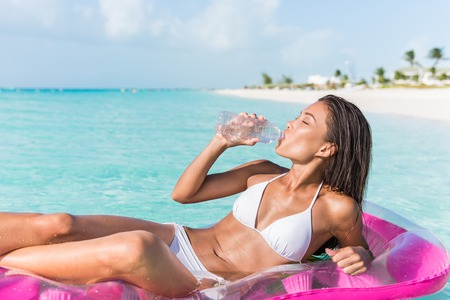 Beach vacation woman on Caribbean holiday drinking fresh and clean water from plastic bottle for healthy hydration while relaxing swimming on ocean float air mattress in tropical resort.