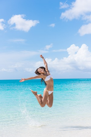 Happy bikini woman having fun jumping of joy and happiness on beach splashing water in perfect turquoise water. Asian girl cheering winning for Caribbean vacation destination during summer travel. Archivio Fotografico
