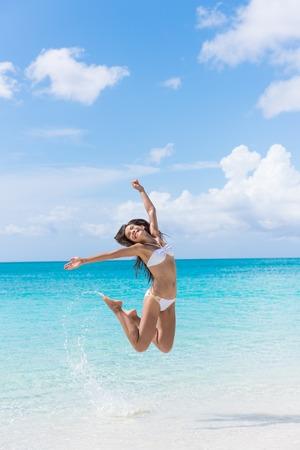 Glückliches Bikinifrau, die Spaß Springen der Freude und Glück am Strand Spritzwasser in perfekter türkisfarbenem Wasser. Asiatische Mädchen für Karibik Urlaubsziel im Sommer Reise Jubel zu gewinnen. Standard-Bild