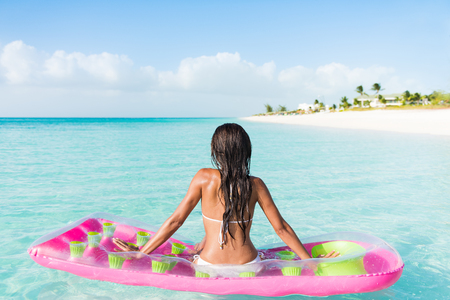 float: Beach relaxation woman floating on pink inflatable air bed pool mattress toy float in ocean beach background in pristine blue turquoise water at luxury caribbean getaway resort.