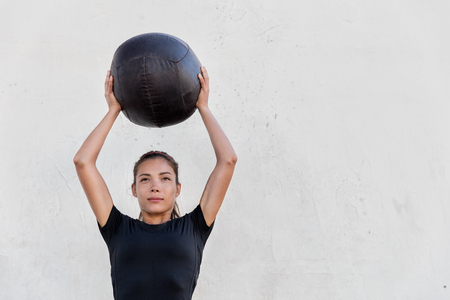 weighted: Fitness crossfit girl holding medicine ball above head for shoulder press workout in outdoor crossfit gym. Young Asian athlete girl doing upper body exercise working out with heavy weighted balls.