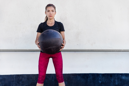 Fitness woman training arms doing biceps curls exercises holding medicine ball in outdoor crossfit gym. Young Asian athlete girl doing upper body strength training workout with heavy weighted balls. Stok Fotoğraf