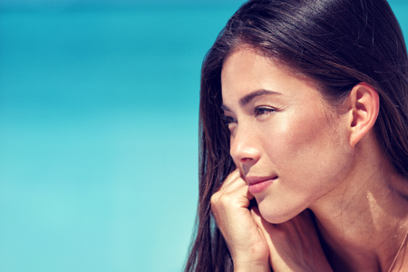 Jonge Aziatische schoonheid vrouw gezicht close-up portret. Gemengd ras Chinees blanke meisje profiel met een gezonde stralende huid en natuurlijke make-up op de wangen, oogleden, wenkbrauwen, lippen. Skincare concept. Stockfoto