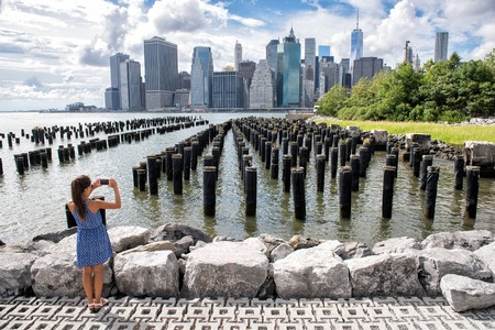 manhattan bridge: New York tourist woman taking mobile picture with smartphone. Manhattan city skyline waterfront lifestyle. People walking enjoying view of downtown from the Brooklyn bridge park Pier 1 salt marsh.