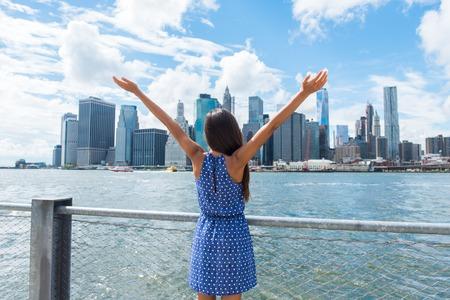 Glückliche freie Frau Jubel in NYC New York City städtischen Skyline mit erhobenen Armen nach oben in den Himmel. Erfolg im Geschäft Karriere, die Zielerreichung oder sorgloser Freiheit erfolgreiche Stadt Person Konzept.