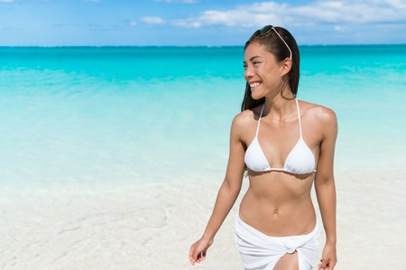 suit skirt: Asian woman relaxing walking on beach in white bikini and cover-up wrap swimwear in turquoise ocean background at Caribbean tropical destination. Stock Photo