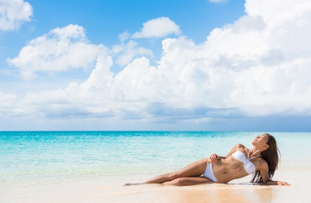 sun tanning: Sexy bikini body woman relaxing sun tanning on beach vacation lying down sunbathing on beach at tropical luxury destination in the Caribbean. Fashion, skincare solar protection, weight loss concept.