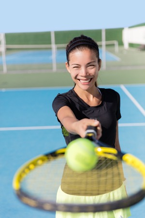 Tennis girl holding racquet  tennis racket and ball on court. Asian woman sport athlete showing sports equipment on outdoor summer club for fitness workout. Attractive ethnic person smiling.