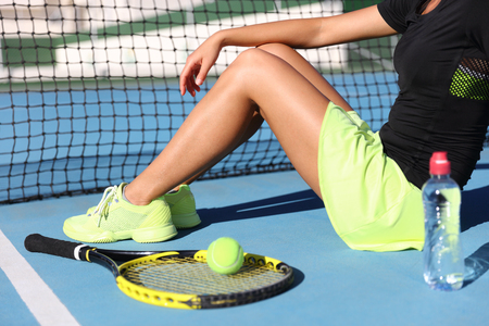 Lower body closeup of tennis player woman resting sitting on outdoor court showing racket , ball and water bottle wearing yellow sportswear outfit. Sports shoes and skirt.