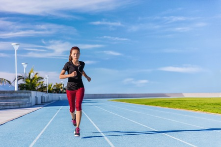 weight loss success: Female Asian athlete runner running on blue tracks at outdoor stadium in summer. Sporty woman jogging listening to music with earphones training cardio for weight loss success. Wellness and health.