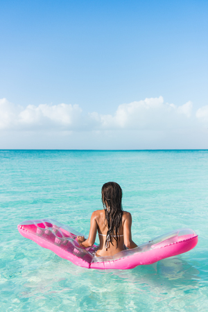 float: Beach vacation woman relaxing on ocean water bed. Beautiful woman from the back sitting on a pink pool float air mattress looking at view of the perfect turquoise pristine sea in tropical destination.