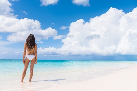 Bikini Frau mit schlanken sexy Körper von hinten auf tropischen weißen Sandstrand in Karibik stehen über die perfekte türkisfarbene Meer suchen. Luxus leben Urlaubsziel. Standard-Bild