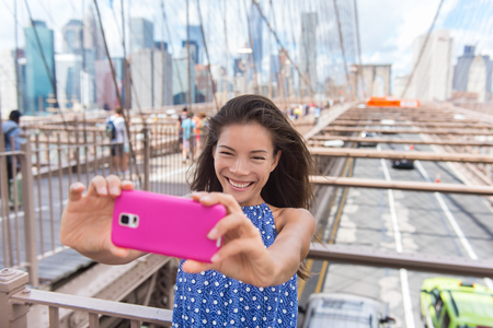 city building: Happy New York City selfie tourist young woman taking a self-portrait photo with smartphone app on Brooklyn Bridge, NYC, Manhattan, USA. Asian girl doing mobile phone photography for social media.