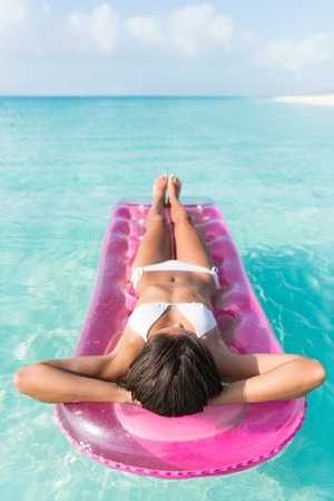 float: Beach vacation woman relaxing in pink plastic pool toy air bed float floating on ocean water on tropical vacation seen from above lying down lounging and sunbathing. Stock Photo