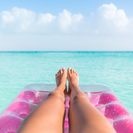 floating: Summer vacation girl lower body closeup. Woman tanning legs  relaxing in ocean on pink inflatable swimming pool air mattress bed floating in turquoise water background. Suntan at tropical beach.