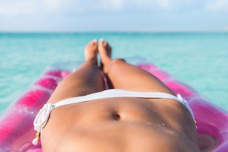 pies sexis: cuerpo de bikini primer plano abs estómago sexy y piernas bronceadas de la mujer playa de bronceado en la cama de colchón de aire en el océano turquesa o una piscina que se relaja en un destino del Caribe tropical.