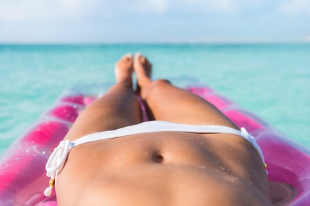 girls bottom: Sexy bikini body abs stomach closeup and tanned legs of beach woman relaxing tanning on air mattress bed on turquoise ocean or swimming pool at a tropical caribbean destination. Stock Photo