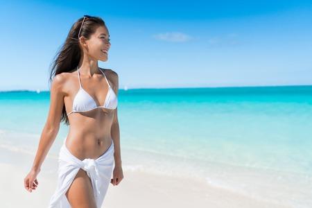 Bikini Frau in der weißen Sonnenschutz Bademode zu Fuß auf tropischen karibischen Strand mit türkisfarbenem Meerwasser in den Sommerferien zu entspannen. Glückliche Lifestyle asiatischen Mädchen.