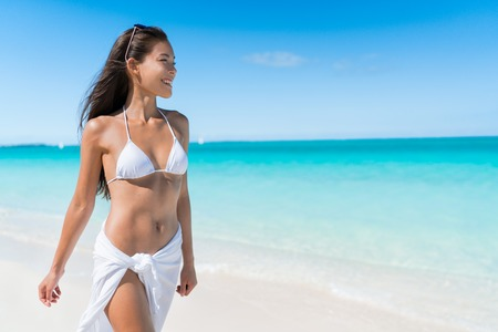 young bikini: Bikini woman relaxing in white sun protection beachwear walking on tropical Caribbean beach with turquoise ocean water during summer vacations. Happy lifestyle Asian girl.