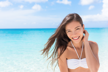Happy beach Asian woman living a healthy lifestyle. Beautiful young mixed race girl smiling at camera wearing white bikini top on tropical Caribbean vacation with hair in the wind. Stock Photo