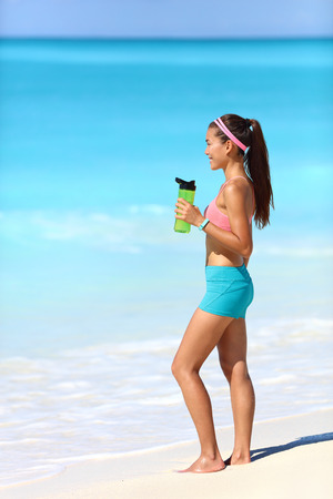 hydration: Beach runner woman taking running break drinking water standing on white sand. Healthy fit girl wearing smartwatch activity tracker bracelet holding bottle for hydration during exercise.