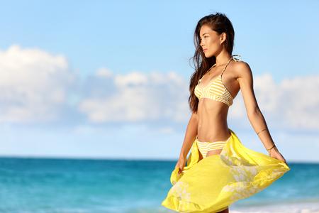 nadar: La mujer asiática atractiva con un cuerpo de bikini delgado estómago se relaja en la puesta del sol con pareo amarillo trajes de baño y ropa de playa encubrimiento disfrutando de su pérdida de peso en la playa vacaciones de verano en el Caribe. Foto de archivo