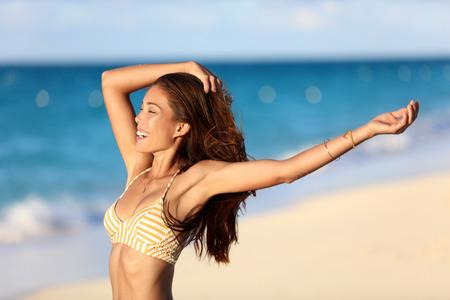 Zorgeloze vreugde vrijheid bikini vrouw gelukkig op het strand gevoel gratis met armen omhoog bij zonsondergang op de oceaan achtergrond. Portret van sexy lichaam Aziatische meisje lachend voor huidverzorging of gewichtsverlies concept.