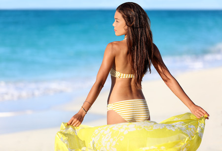 Beach woman relaxing in yellow bikini and cover-up pareo beachwear enjoying sunset. Beautiful Asian girl model from the back for suntan skincare or weight loss cellulite body concept.