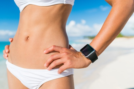 Fit bikini woman wearing wearable tech smartwatch. Closeup of slim abs stomach and beachwear on of female person relaxing on beach with activity tracker wrist band on summer holidays. Stock Photo
