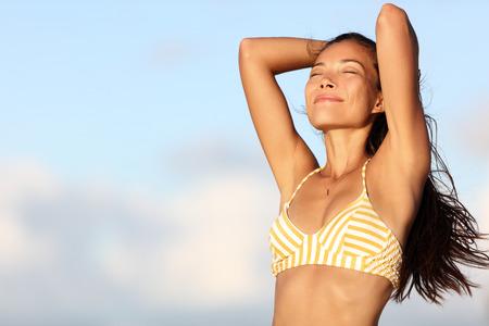 Ontspannende bikini vrouw gevoel goed en gratis in de buitenlucht natuur inademen van frisse lucht met de armen omhoog tonen gezond lichaam en gladde huid en oksels voor laser-epilatie behandeling. Aziatische model op het strand.
