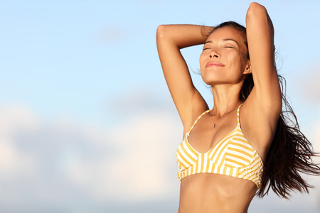 armpits: Relaxing bikini woman feeling good and free in outdoor nature breathing fresh air with arms up showing healthy body and smooth skin and armpits for laser epilation treatment. Asian model on beach.