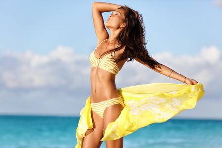 tratamientos corporales: Mujer del bronceado atractivo joven que disfruta de la puesta del sol en la playa con ropa de playa envoltura de encubrimiento que muestra el cuerpo de bikini delgada para bajar de peso y el concepto de depilación cuidado de la piel. Modelo asiático tomar el sol durante las vacaciones de verano.