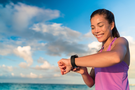 Active girl using fitness tracker smart watch jogging on summer nature outdoors looking at health data during sports activity touching the screen of her smartwatch. Stock Photo