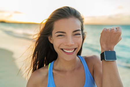 girl with a wristwatch: Smartwatch happy girl showing display screen on trendy new smart watch fitness tracker wristwatch. Healthy young Asian sporty woman smiling on beach vacation running at sunset living an active life.