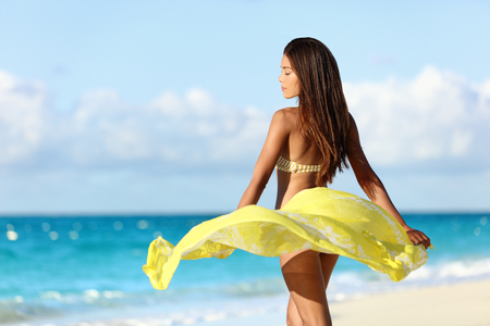 Carefree beautiful sexy bikini body woman relaxing in yellow flowing cover-up beachwear fashion wrap on ocean sunset background. Weight loss thighs cellulite and skincare spa beauty care concept. Stock Photo