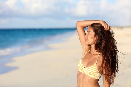 Carefree bikini woman enjoying sunset on beach. Beautiful relaxing Asian model caressing hair with closed eyes over the ocean on summer travel vacation in yellow swimsuit top in tropical destination.