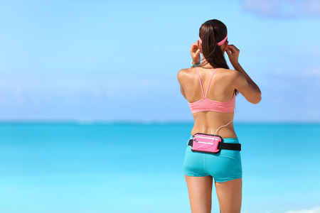 back packs: Runner girl getting ready for run on beach listening to music with earphones and smartphone holder fanny pack waist belt as sports gear wearing wearable tech activity tracker.