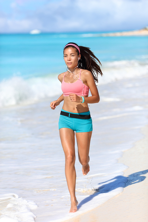woman barefoot: Fitness running runner exercising cardio with smartwatch activity tracker jogging barefoot on white sand beach living an active healthy lifestyle. Asian fit woman with wearable tech.