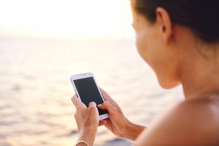 Smartphone femme textos sur l'application des médias sociaux regardant l'écran d'affichage pour sms lecture sur l'océan fond sur un balcon de croisière en mer ou sur la plage au coucher du soleil sur les vacances. fille Unrecognizable utilisant un téléphone intelligent. Banque d'images - 54454572