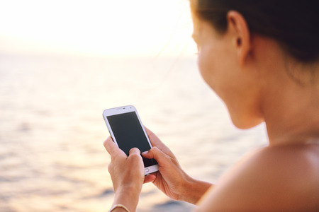 sms: Smartphone woman texting on social media app looking at display screen for sms reading on ocean background on a sea cruise balcony or beach at sunset on holiday. Unrecognizable girl using smart phone.