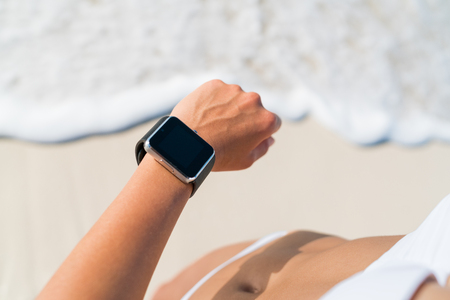sport fitness: Active lifestyle woman looking at wearable tech smartwatch. Closeup of arm on beach with touch screen on wrist band of person relaxing in the water with activity tracker wrist band in outdoor living.