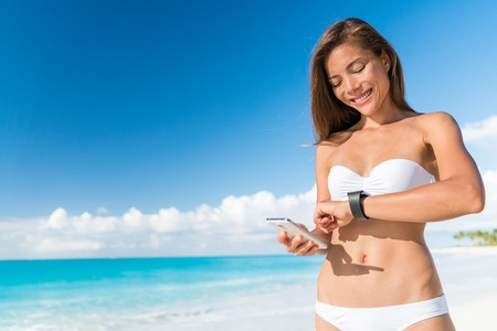 wearable: Bikini woman using smart phone syncing watch data for smartwatch app on smartphone. Happy Asian girl on beach summer holidays in tropical destination looking at screen of activity tracker device. Stock Photo