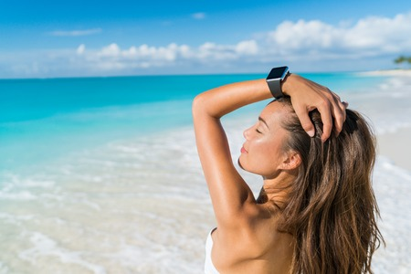 asian bikini: Smartwatch woman relaxing on beach wearing smart wrist watch for activity tracker for an active lifestyle on tropical Caribbean travel destination during summer vacation. Sexy Asian model sun tanning. Stock Photo