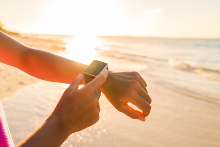 Smart watch woman using smartwatch touching button and touchscreen on active sports activity or morning jogging during beach sunrise or sunset. Closeup of hands and wrist with smart watch screen. Stock Photo - 54454711