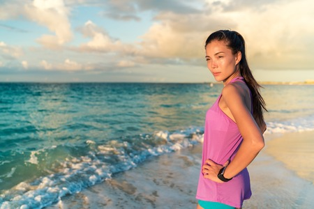 resting heart rate: Smartwatch woman with wearable tech watch on her wrist enjoying sunset on beach living a healthy active life. Asian fitness girl taking a break from jogging or sports activity. Stock Photo