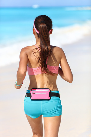 fanny: Active runner from behind jogging with wearable tech running gear fanny pack smartphone holder belt for music listening with earphones jogging away in blue sport shorts and sports bra with ponytail.