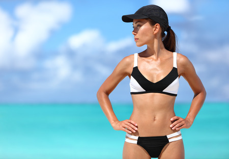 Sexy sporty bikini woman ready for beach sports. Active healthy Asian girl model standing against ocean background on sunny summer travel vacation. Stock Photo