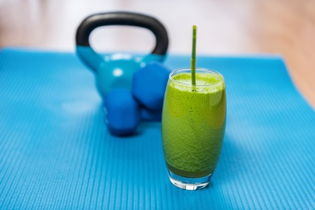 free weights: Weight loss healthy eating green vegetable smoothie with free weights kettlebells and exercise mat in gym center. Health and fitness concept. Vegetarian diet and nutrition for strength training.