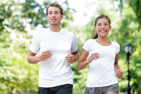 hacer footing: Aptitud estilo de vida saludable. la formación de verano feliz pareja ejecuta Marathon en el Central Park de Manhattan, Nueva York. modelo de mujer asiática y caucásica de deporte de aptitud atleta masculino disfrutando de trotar juntos.